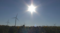 Wind turbine in sunflower sun silhouette with bright ray electric power farm day Stock Footage