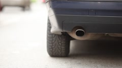 Rear view on car discharge pipe, low camera position, plastic bumper - stock footage