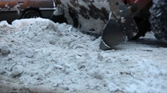 Backhoe loader plow out dirty snow from road, close up view to steel bucket Stock Footage