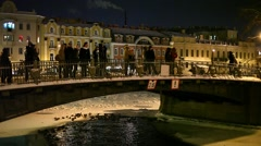 People stay on city bridge at winter night, historical downtown buildings Stock Footage