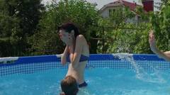 Swimming pool. Young woman and children playing in the pool. Slow motion. HD Stock Footage