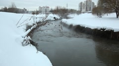 Small river with black polluted water purl between snowy banks, brume rise up Stock Footage