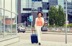 happy young african woman with travel bag in city - stock photo