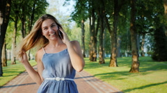 Carefree young woman walking along a path in the park, talking on the phone Stock Footage
