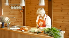Elderly woman slices carrots and answers the call. Stock Footage