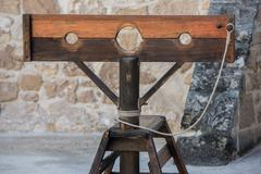 Old wooden pillory close up on castle stone wall background - stock photo
