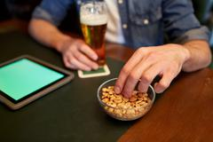 man with tablet pc, beer and peanuts at bar or pub - stock photo