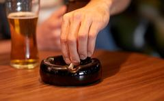 close up of hand extinguish cigarette in ashtray - stock photo