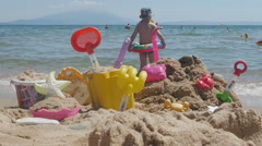 Colorful toys on sandy beach - close up, little boy trying to get in sea water. Stock Footage