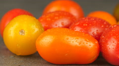 Camera pans across assorted cherry tomatoes with water drops Stock Footage