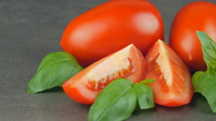 Camera pans across red plum tomatoes and basil Stock Footage