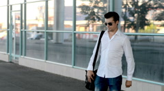 A young man walks, serious and looks around, waiting for someone Stock Footage
