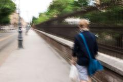 Long exposure abstract shot of a man with shopping bags walking through the city Stock Photos