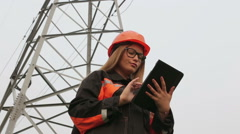 Woman engineer working near an electrical substation lines, power lines, teamwor Stock Footage