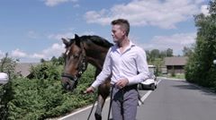 The man walking withe horse on the road Stock Footage