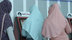 Muslim Women Using Self-Service Check-In Kiosk - stock footage
