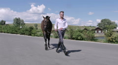 Young man walking with horse near the horse club Stock Footage