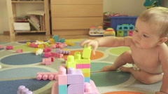 Little baby boy playing constructor in the room on the floor. Designer toy. Stock Footage