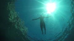 SLOW MOTION UNDERWATER: Young man swimming below the water surface in ocean Stock Footage