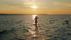 Girl dancing in the sea in the sunset Stock Footage
