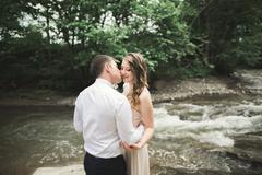 Elegant gentle stylish groom and bride near river with stones. Wedding couple in - stock photo