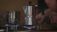 Italian Mocca coffeepot and pan on cooker Stock Footage