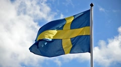 A Swedish flag flutters in the wind against a blue sky background Stock Footage