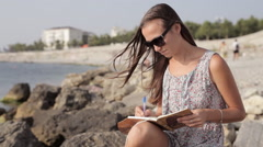 Yong woman making notes in diary on the beach Stock Footage