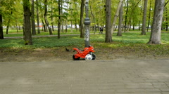 Children's motorcycle parked in a public park Stock Footage