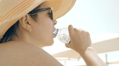 A thirsty female is drinking water at the beach - stock footage