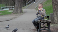 Schoolboy eating on a bench Stock Footage