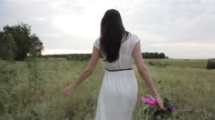 Girl goes on the field with a bouquet Stock Footage