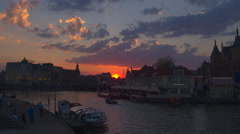 Crowded streets of Amsterdam and lively boat transport in river canal at sunset Stock Footage