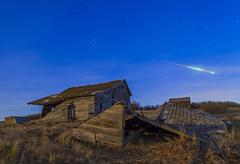 A bright bolide meteor breaking up as it enters the atmosphere. - stock photo