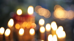 Many wax yellow candles brightly burn in church Stock Footage