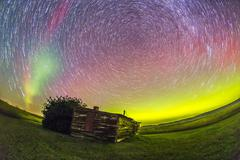 Fish-eye lens composite of aurora and circumpolar star trails above ranch in Stock Photos