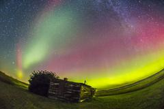 Fish-eye lens view of the northern lights above an old ranch in Canada. - stock photo