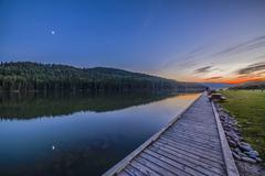 Quarter moon reflected in the waters of Reesor Lake, Alberta, Canada. - stock photo