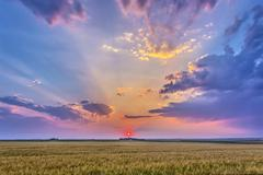 Prairie sunset with crepuscular rays in Alberta, Canada. Stock Photos