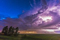 A massive thunderstorm lit internally by lightning. Stock Photos
