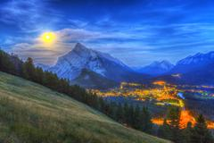 Supermoon rising over Mount Rundle and Banff townsite in Canada. Stock Photos