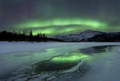 Reflected aurora over a frozen Laksa Lake, Nordland, Norway. Stock Photos