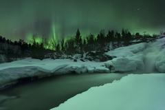 A wintery waterfall and aurora borealis over Tennevik River, Norway. Stock Photos