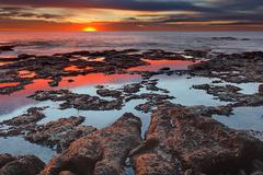 Tidal pools reflect the sunrise colors during the autumn equinox. Stock Photos
