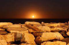 The moon rising behind rocks lit by a nearby fire in Miramar, Argentina. Stock Photos