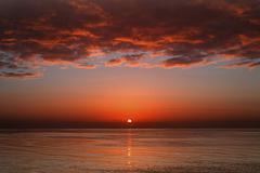 A layer of clouds is lit by the rising sun over Rio de la Plata, Buenos Aires, Stock Photos