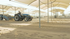 A man is sieving sand in a tractor on a beach Stock Footage