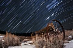 Abandoned farm equipment against a backdrop of star trails. - stock photo