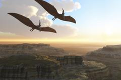 Two Pterodactyl flying dinosaurs soar above a beautiful canyon. - stock illustration