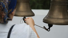 Woman rings in temple bells pulling rope that she keeps in her right hand Stock Footage